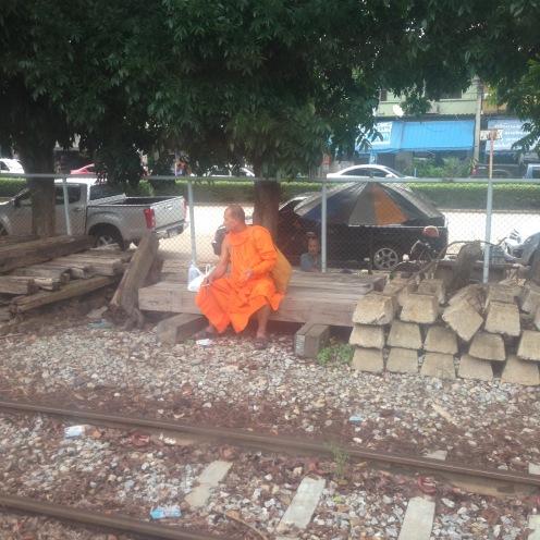 A monk waiting for a train enjoying a smoke!