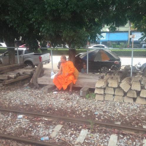 A monk waiting for a train enjoying a smoke!