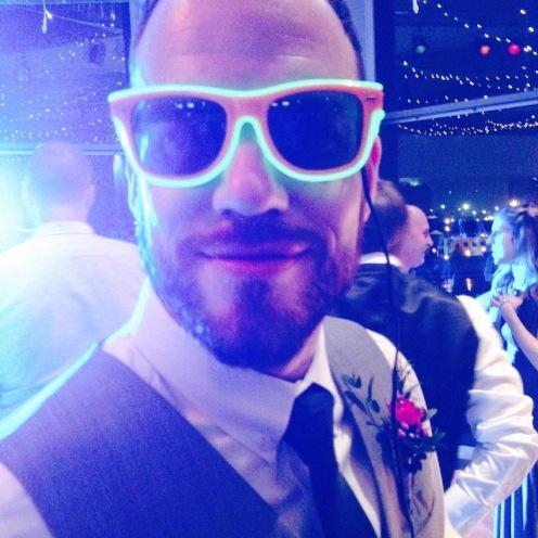The husband on the dance floor looking slightly neon